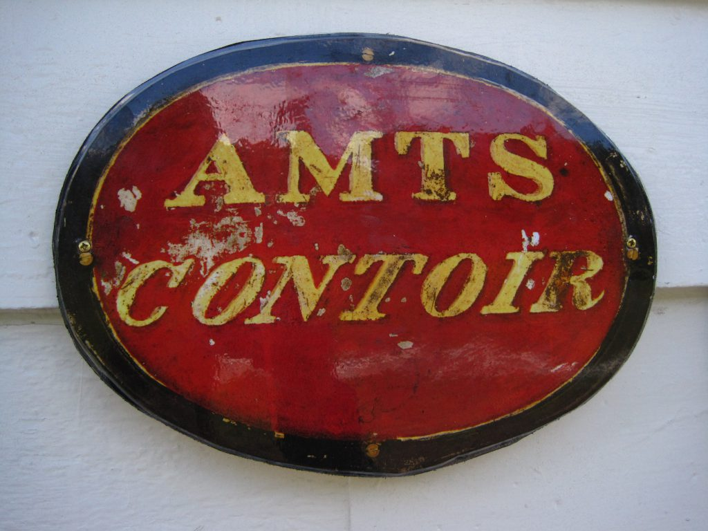 """Bilete av teksten """"Amts Contoir"""" i gullbokstavar på raudt, ovalt skilt."""